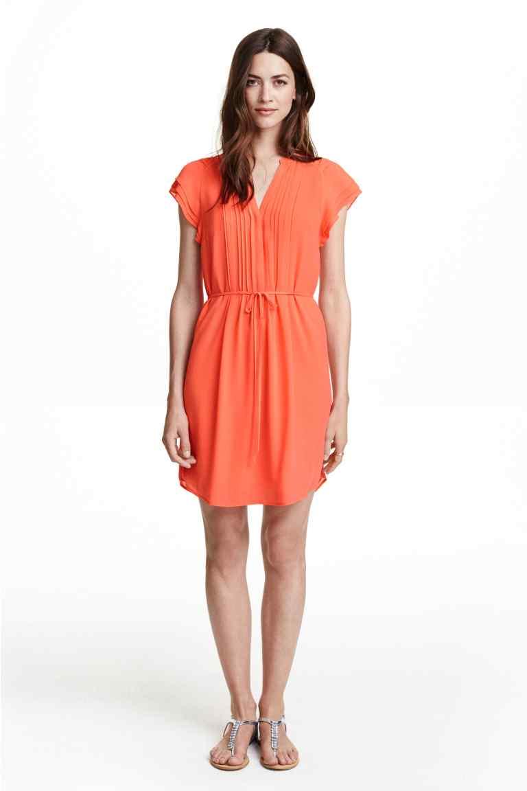 Abito corto arancione con maniche a farfalla e cintura in vita. Prezzo 29,99 €
