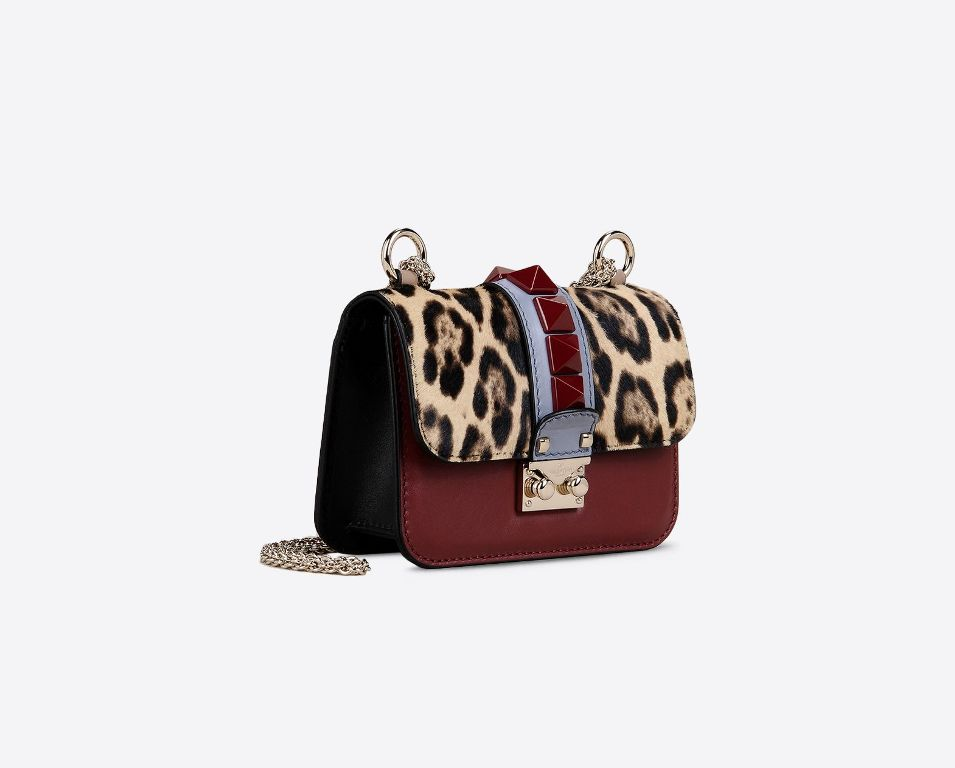 Mini shoulder bag con catena. In vitello multicolor e cavallino maculato. Maxi borchie laccate in dark red. Tracolla removibile (1450 €)