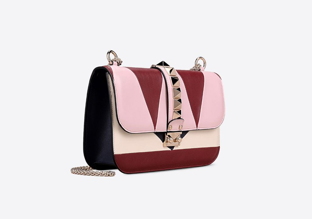Shoulder bag con catena. In vitellino, presenta intarsi geometrici multicolore. Borchie rifinite in platino. (1780 €)