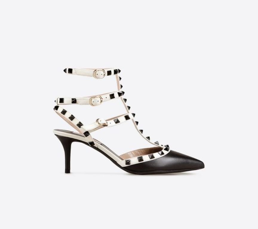 Ankle strap Rockstud in vitello nero e listini Light Ivory. Borchie laccate in nero. Tacco 65 mm (730 €)